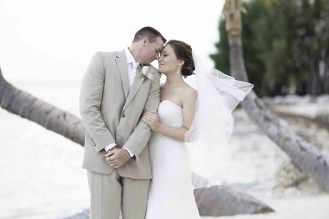 Newly married couple posing for photo at bent palms on beach