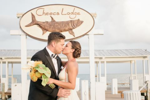 Newly married couple kissing on pier