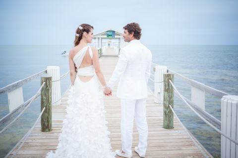 Newly married couple posing for a photo on the pier.