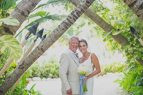 Newly married couple posing for a photo under crossed palms archway