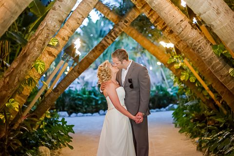 Newly married couple kissing under the crossed palms archway