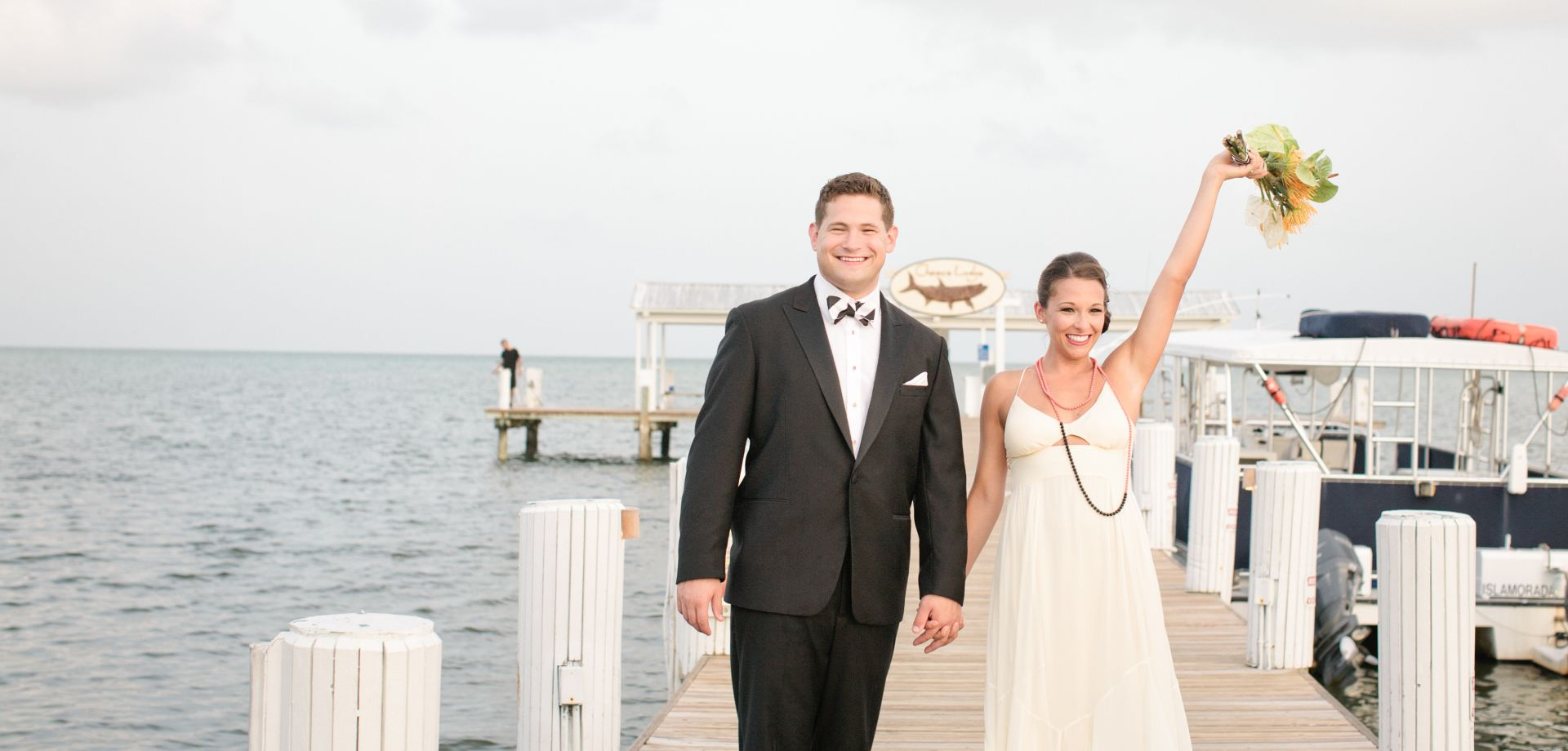 Couple posing for a photo after getting married, on pier