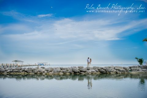 Far away photo of couple holding eachother on a rocky edge along the water