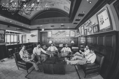 Black and white photo of groomsmen relaxing in lodge