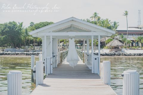 Wedding dress hanging from the covered area on the pier.
