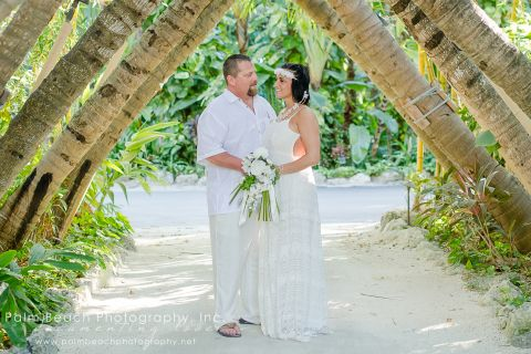 Newly married couple posing for a photo under crossed palms archway.