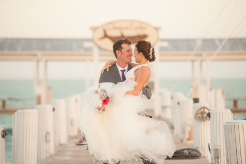 Groom carrying his bride down the pier